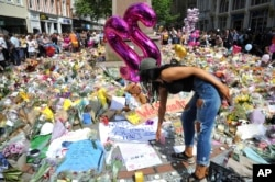 FILE - A young woman views of flower tributes for the victims of the explosion at St. Ann's square in central Manchester, England, May 25, 2017.