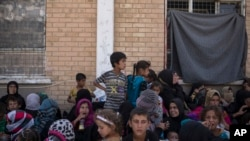 Perempuan dan anak-anak dari Hawija duduk di luar Pusat Pemeriksaan Kurdi, di Dibis, Irak, untuk menentukan ada atau tidaknya keterkaitan mereka dengan ISIS, 3 Oktober 2017. (Foto: dok).