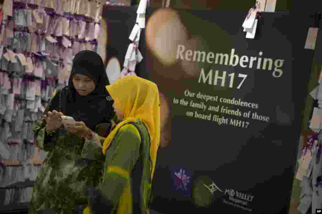 Shoppers take photos next to prayer notes for passengers aboard Malaysia Airlines Flight MH17 at a shopping mall in Kuala Lumpur, July 24, 2014.