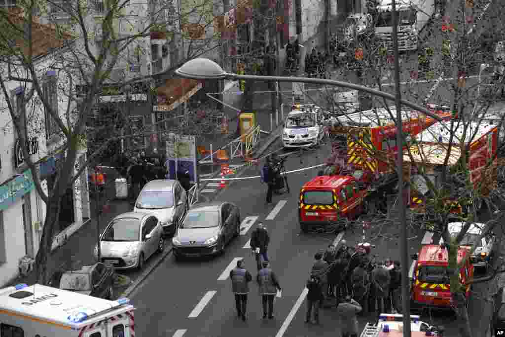 Police officers, firefighters and rescue workers gather at the site of a shooting in Montrouge, south of Paris, Jan. 8, 2015.
