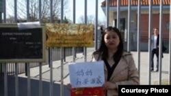 中国异议作家李剑虹在瑞典举牌要求回国(参与网图片)