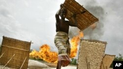 An unidentified woman carries her tapioca after drying it near a gas flare belonging to the Shell oil company in Utorogun, Nigeria, March 5, 2006 (file photo).