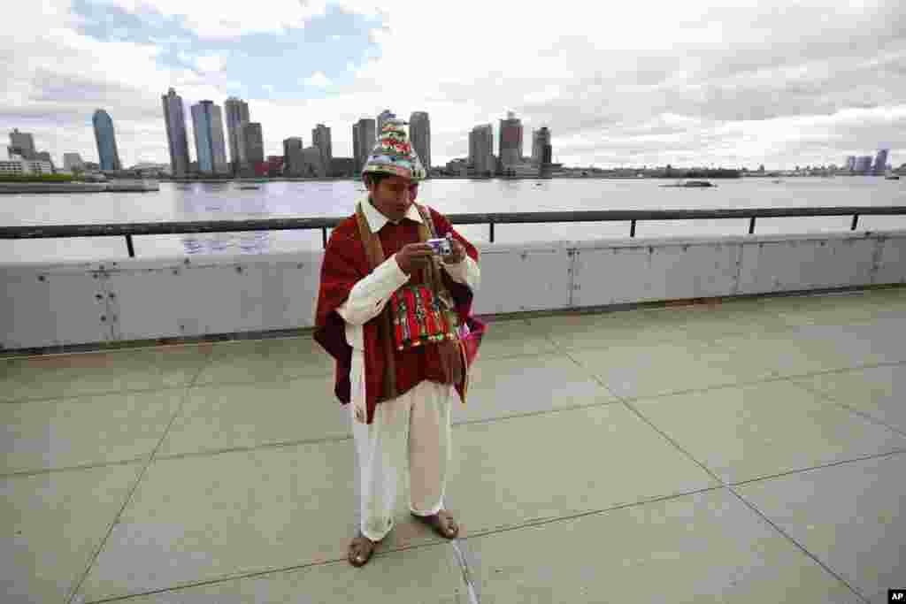 Tomas Mamani dari La Paz, Bolivia, melihat kameranya setelah mengambil foto di luar markas besar PBB di New York (22/9). (AP/Jason DeCrow)