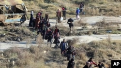 This photo provided by the Rumaf, a Syrian Kurdish activist group, which has been authenticated based on its contents and other AP reporting, shows people fleeing rebel-held eastern neighborhoods of Aleppo, Nov. 27, 2016.