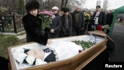 Nataliya Magnitskaya (L), mother of Sergei Magnitsky, grieves over her son 's body during his funeral at a cemetery in Moscow November 20, 2009.