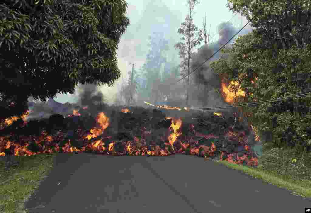 In this photo provided by the U.S. Geological Survey, a lava flow moves across Makamae Street in the Leilani Estates neighborhood near Pahoa on the island of Hawaii. The Kilauea volcano has destroyed more than 25 homes since it began shooting lava into the air last week, and residents who evacuated do not know how long they might be displaced.