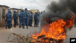 Burundian riot police march past a burning tyre roadblock following clashes with opposition protesters in a street in the capital Bujumbura, April 26, 2015.