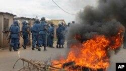 Des policiers antiémeutes marchent contre des manifestants dans les rues de Bujumbura, le 26 avril 2015.