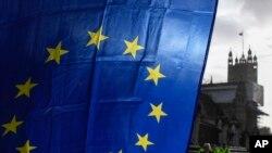 Bendera Uni Eropa dipegang oleh seorang demonstran, dengan latar belakang Menara Victoria, di luar Istana Westminster, di London, Senin, 14 Desember 2020, selama protes saat pembicaraan perdagangan Brexit berlanjut. (Foto: Foto AP/Alberto Pezzali)