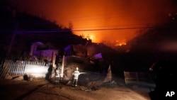 4月13日在智利港口城市瓦尔帕莱索,消防队员站在被大火吞噬的房屋旁
