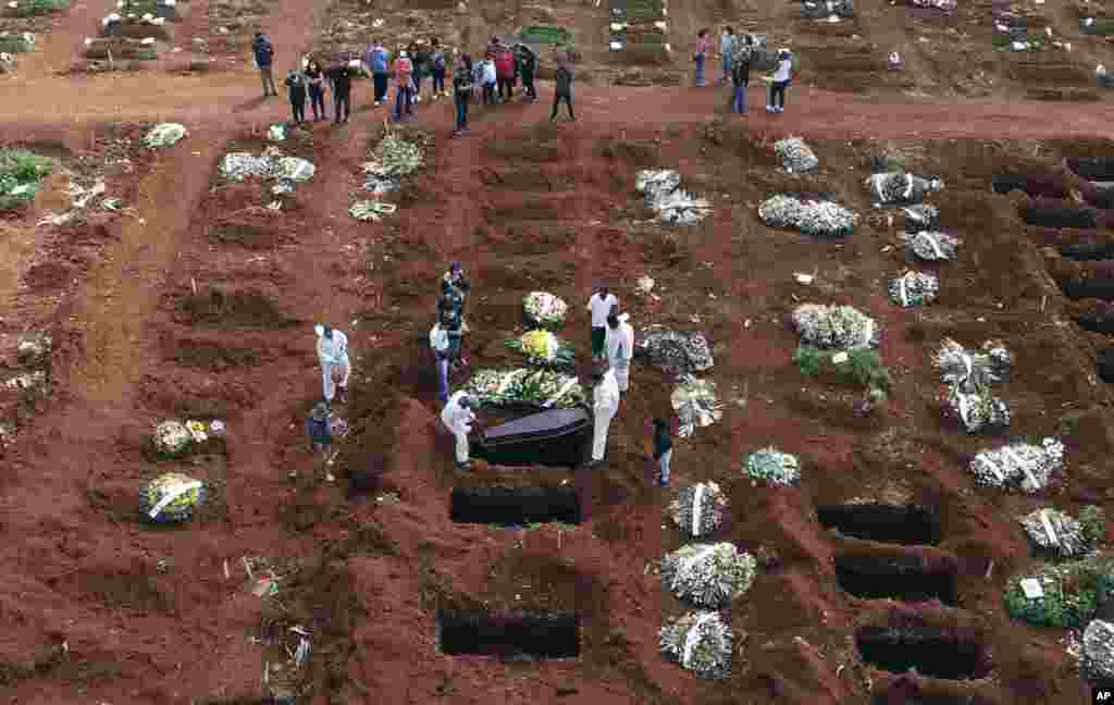 Cemetery workers wearing protective gear lower the coffin of a person who died from complications related to COVID-19 into a gravesite at the Vila Formosa cemetery in Sao Paulo, Brazil, April 7, 2021.