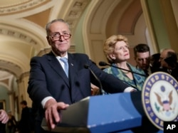 Senate Minority Leader Chuck Schumer, D-N.Y., with Sen. Debbie Stabenow, D-Mich., right, meets with reporters on Capitol Hill before President Donald Trump's speech to the nation, in Washington, Feb. 28, 2017.