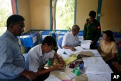 A Myanmar army officer, second right, checks whether his name is on the eligible voters list at a township Election Commission office in Mandalay, Myanmar, Nov. 5, 2015.
