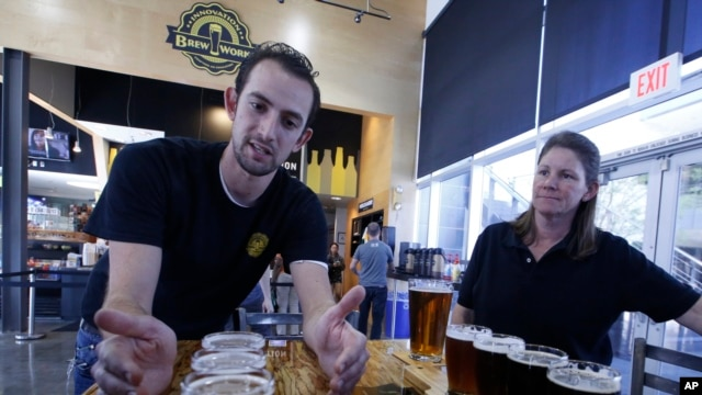 Koby Harris, brewery production manager, left, and Sandra Cain, assistant director of retail operations, present freshly brewed beers at Innovation Brew Works, California State Polytechnic University in Pomona, Calif., March 19, 2015.