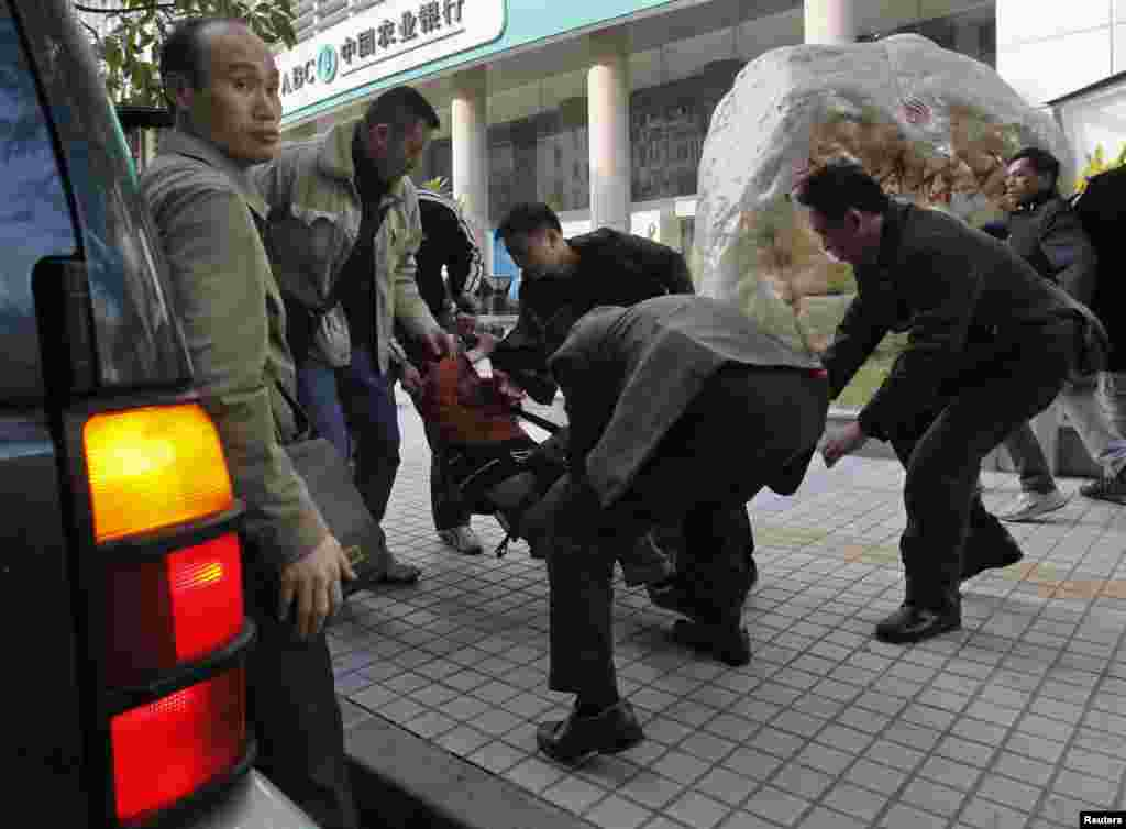 A protester is taken away by plainclothes police officers and placed in a jeep near the office of Southern Weekly newspaper in the southern Chinese city of Guangzhou, January 10, 2013.