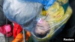 Một em bé di cư ngủ dưới trời mưa lạnh giá tại cửa khẩu biên giới từ Slovakia vào Croatia, ngày 19/10/2015.