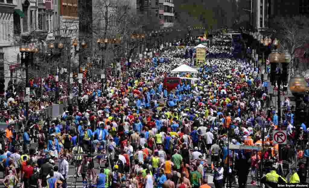 Wakimbiaji wa mbiyo za marathon za Boston wakipita mtaa wa Boylston baada ya kukamilisha mbiyo za marathon za Boston 2014