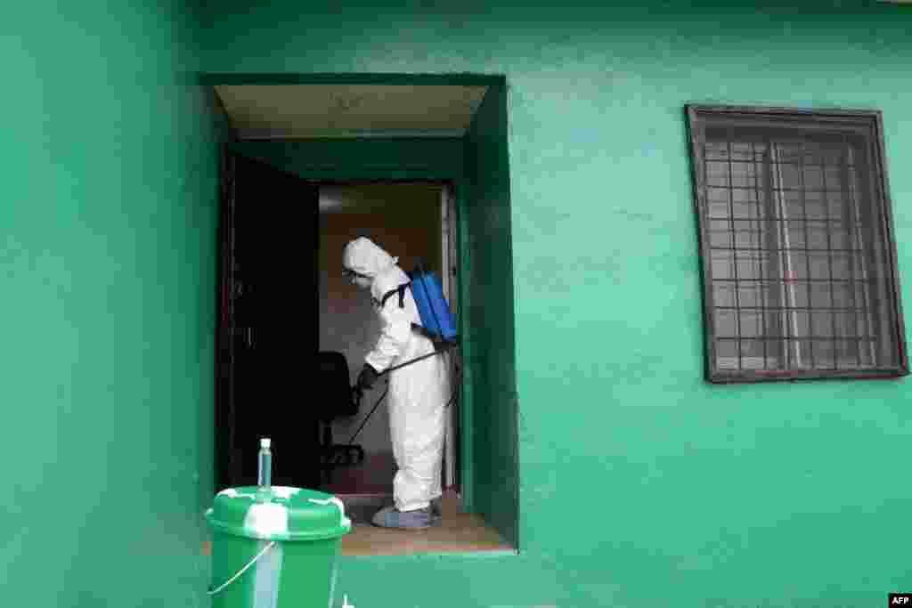 Một công tác viên y tế khử trùng một ngôi nhà trong một cuộc diễn tập phòng chống Ebola tại Monrovia, Liberia. Tổ chức Y tế Thế giới hôm thứ Năm nói rằng số ca nhiễm Ebola đã tăng lên nhanh chóng và có thể vượt quá 20.000 người trước khi virus được kiểm soát.