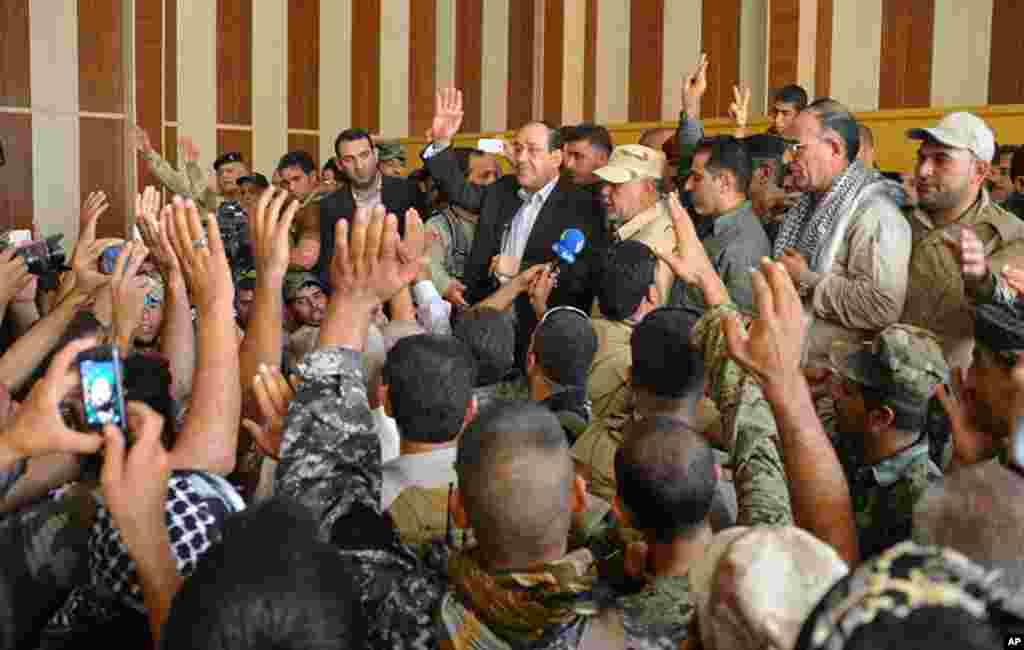 In this photo provided by the Iraqi government, outgoing Prime Minister Nouri al-Maliki, center, is surrounded by residents and security forces after his arrival in Amerli, some 170 kilometers north of Baghdad, Iraq, Sept. 1, 2014.