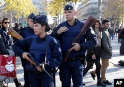 FILE - French police patrol at the Monument a la Republique, in the Place de la Republique in Paris, where people are gathering on Nov. 15, 2015, two days after a series of deadly attacks.