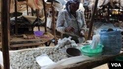 A woman sells odowa stones at a roadside market in Nairobi, Kenya (R. Ombuor/VOA).