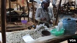 A woman sells odowa stones at a roadside market in Nairobi, Kenya (R. Ombuor/VOA). Seorang perempuan menjual batu odowa di pinggir jalan