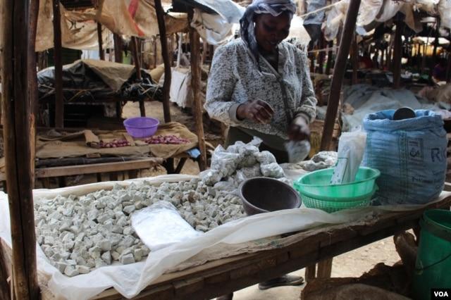 Một phụ nữ bán đá odowa ở một khu chợ ven đường, Nairobi, Kenya (Ảnh: R. Ombuor/VOA).