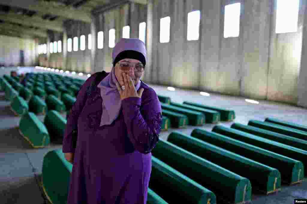 Seorang perempuan terisak dekat peti-peti jenazah para sanak saudaranya yang menjadi korban pembantaian di Srebrenica tahun 1995, di Potocari, Bosnia-Herzegovina. Jenazah 136 korban yang baru diidentifikasi akan dimakamkan 11 Juli, tepat 20 tahun setelah pembantaian di Srebrenica.