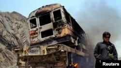 Seorang polisi berjaga di dekat truk NATO yang terbakar akibat serangan roket dan senjata otomatis di Jamrud, wilayah Khyber di Pakistan (10/6). Sedikitnya enam orang dilaporkan tewas dalam insiden serangan militan ini.