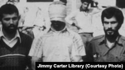 一名美国人质在美国驻德黑兰大使馆外聚集的人群前被游街。(1979年11月9日 资料照片)