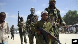 FILE - A young boy leads militant Islamist al-Shabab fighters as they conduct military exercises in northern Mogadishu's Suqaholaha neighborhood, Somalia, Jan. 1, 2010. Dozens of children kidnapped by al-Shabab and being trained as fighters were rescued from a school in the Middle Shabelle region, Somali's information minister said Friday.