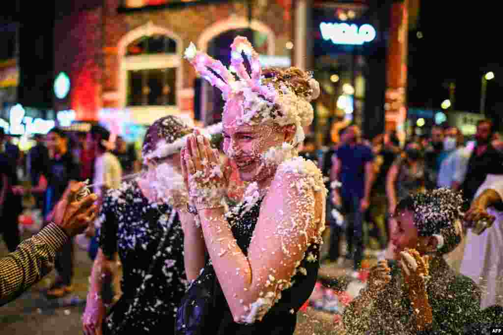 A woman is sprayed with a foam substance as she celebrates the New Year in Kuala Lumpur, Malaysia.