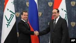 Russian Prime Minister Dmitry Medvedev shakes hands with Iraq's Prime Minister Nouri Al-Maliki outside Moscow, October 9, 2012.
