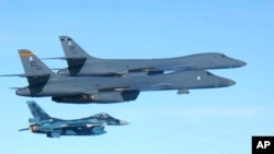 In this photo released by Japan Air Self Defense Force, U.S. Air Force B-1B bombers, top, fly with a Japan Air Self Defense Force F-2 fighter jet over Japan's southern island of Kyushu, just south of the Korean Peninsula, during a Japan-U.S. joint exercise, July 30, 2017.