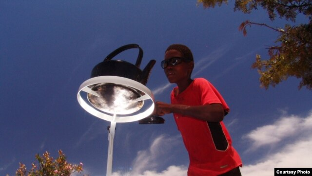 A boy tends a kettle boiling one on of the parabolic cookers (Photo: Sunfire)