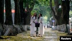 Nữ sinh Việt Nam chụp ảnh kỷ niệm trên đường phố Hà Nội.