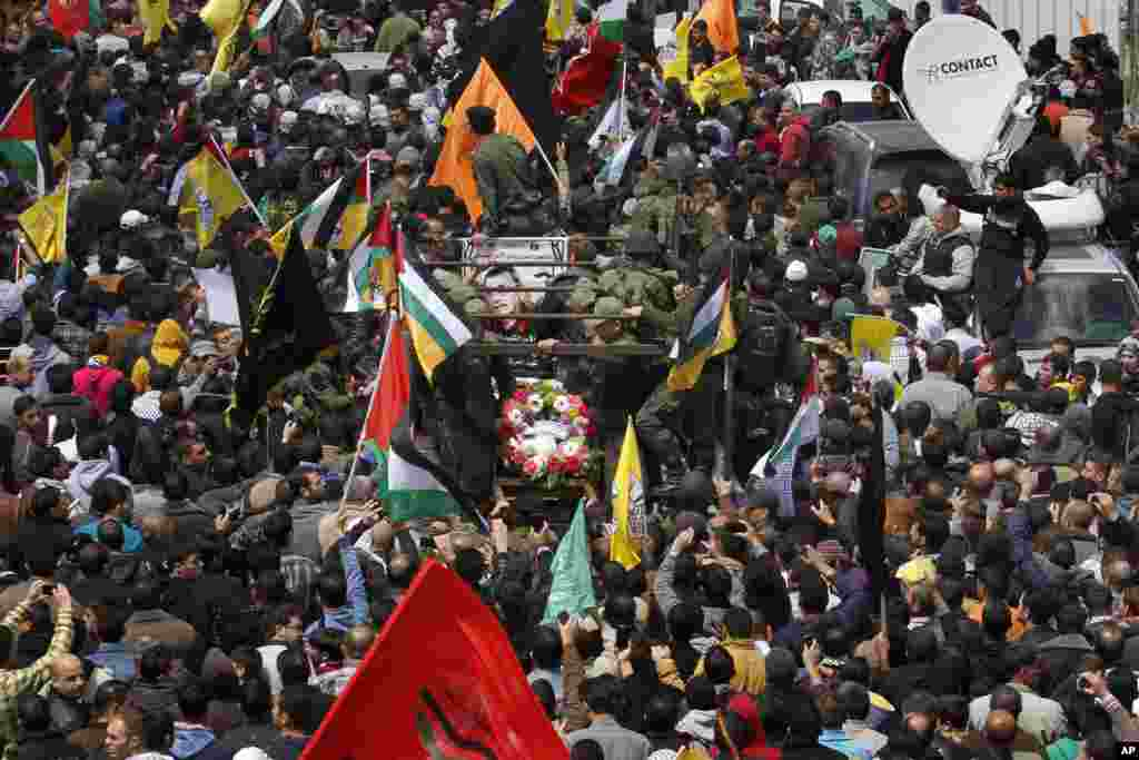 Palestinians take part in the funeral of Maysara Abu Hamdiyeh in the West Bank city of Hebron, April 4, 2013.