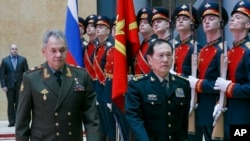 Russian Defense Minister Sergei Shoigu, left, and China's Defense Minister Wei Fenghe review an honor guard prior to their talks in Moscow, Russia, April 3, 2018.