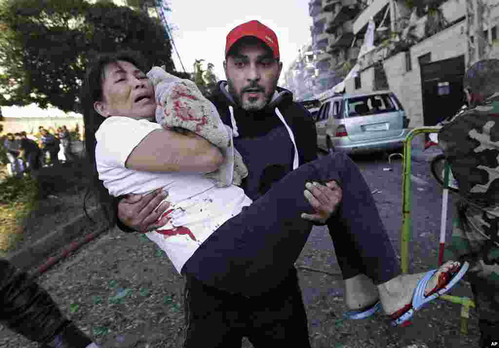 A man carries an injured domestic worker after explosions near the Iranian embassy in Beirut, Nov. 19, 2013.