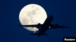 FILE - A passenger aircraft is silhouetted against the rising moon in New Delhi, May 7, 2009.