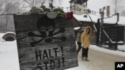 """A rose is placed on top of a sign that reads """"Stop"""" with a skull painted, near the gate at the concentration camp during a ceremony marking the 68th anniversary of the liberation of the Auschwitz and to remember the victims of the Holocaust, in Oswiecim,"""