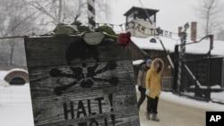 """奥斯威辛集中营大门边树立的""""停止""""标语牌上有玫瑰并画有骷髅"""