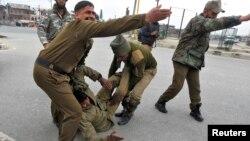 ກຳລັງຮັກສາຄວາມສະຫງົບ ໃນແຄວ້ນ Kashmir ຖ່າຍຮູບໃນຂະນະທີ່ພາກັນຫາມເອົາເພື່ອນຮ່ວມງານ ທີ່ໄດ້ຮັບບາດເຈັບໃນການສູ້ລົບກັບພວກຫົວຮຸນແຮງທີ່ເມືອງ Srinagar ຂອງແຄວ້ນ Kashmir ໃນວັນທີ 13 ມີນາ 2013.