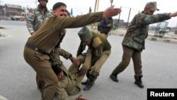 Binh sĩ Ấn Ðộ giúp một đồng đội bị thương trong một vụ nổ súng ở Srinagar, ngày 13/3/2013.