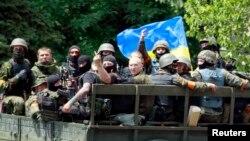 Pasukan Ukraina yang duduk di bak belakang truk terbuka melambaikan tangan kepada penduduk di sekitar lokasi pertempuran di kota pelabuhan Mariupol, Ukraina (13/6).