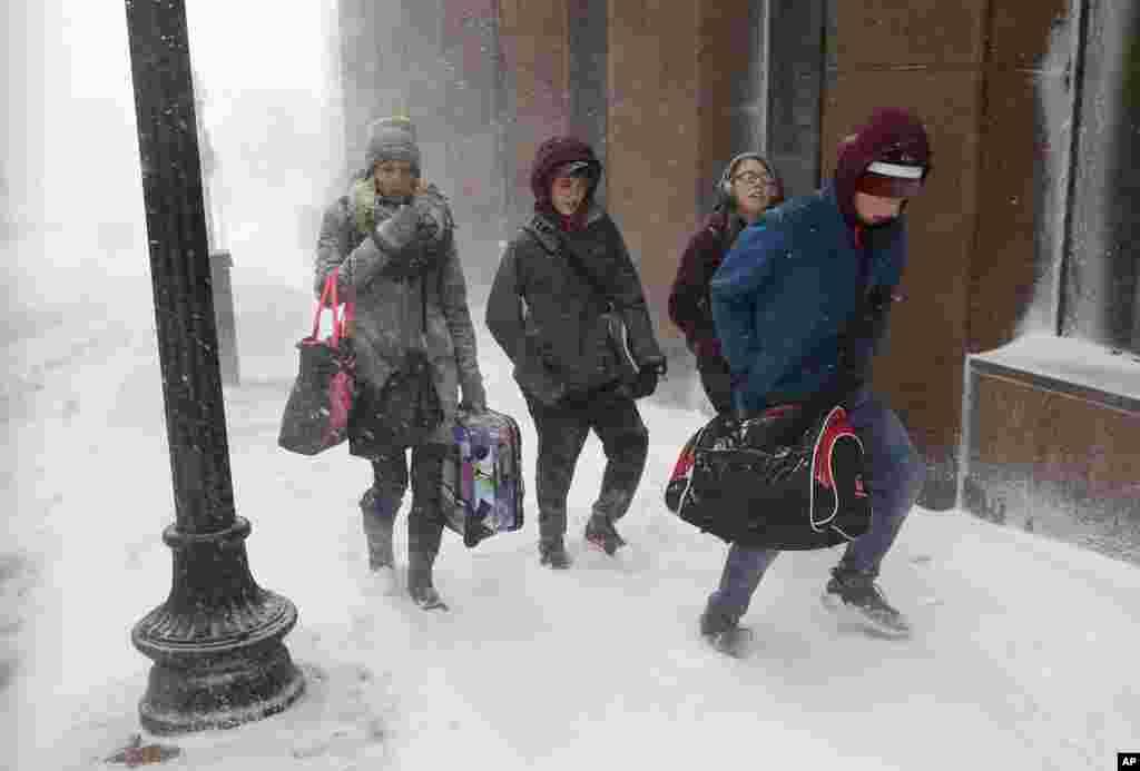 Люди з багажем на вулиці під час снігопаду у Бостоні. 4 січня 2018 року.