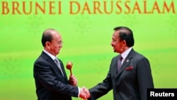 Burmar's President Thein Sein (L), chairman of the next ASEAN Summit, shakes hand with Brunei's Sultan Hassanal Bolkiah after receiving the ASEAN Gavel during the Closing Ceremony of the 23rd ASEAN Summit, Bandar Seri Begawan, Brunei, Oct. 10, 2013.