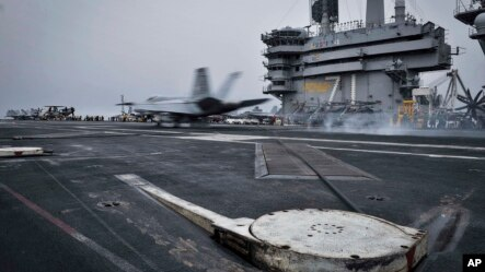 In this Wednesday, April 15, 2015 image released by U.S. Navy Media Content Services, an F/A-18E Super Hornet, assigned to the Knighthawks of Strike Fighter Attack Squadron 136, lands on the flight deck aboard Nimitz-class aircraft carrier USS Theodore Ro