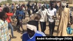 Les étudiants sur les cendres de leur restaurant brûlés par la police entonnant l'hymne national, à N'Djamena, Tchad, le 14 février 2017. (VOA/André Kodmadjingar)