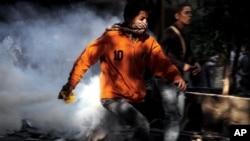 周日开罗解放广场上的埃及抗议者与安全部队发生冲突时四处奔跑